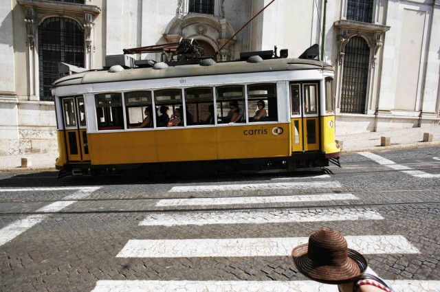 The tram 28 moves past an old building in Lisbon