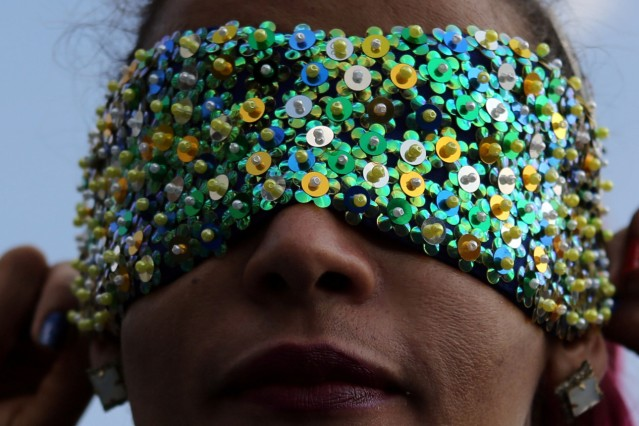 Brazil's Paralympic athlete Terezinha Guilhermina puts on a mask while posing for a photograph at the NAR sports center in Sao Paulo