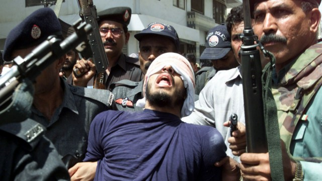 -FILE PHOTO 11SEP02- Security officials escort a gunman (C) arrested after a gunbattle in the southe..