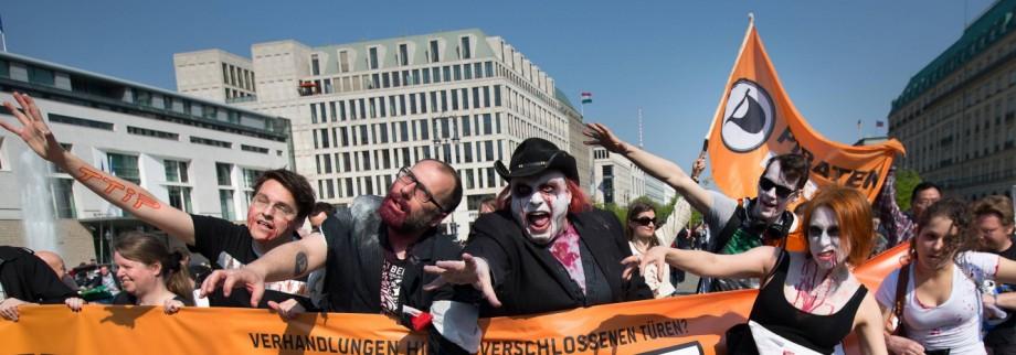 Mitglieder der Piratenpartei protestieren als Zombies am Brandenburger Tor gegen das geplante transa