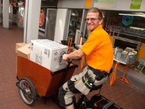 Dorfladen Olympiawerk, Olympiadorf. Sie fangen im Oktober einen ganz neuen Service an, bei dem sie mit E-Lastenrädern Pakete im autofreien Olympiadorf ausliefern.