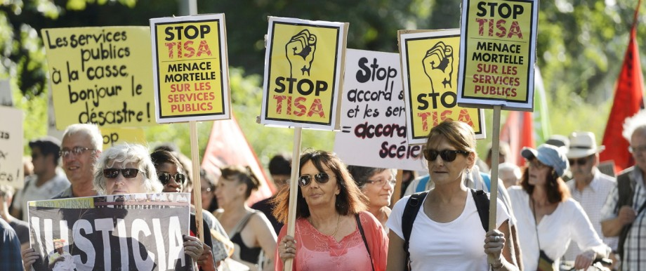 Demonstrators hold posters and banners during a rally against the