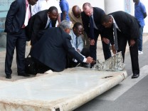 Ministry of Transport Malaysian Senior Accident investigator Aslam Basha Kham inspects a wing suspected to be a part of missing Malaysia Airlines jet MH370 discovered on the island of Pemba, in Dar es Salaam
