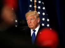 Republican presidential nominee Donald Trump reacts as reporters yell questions to him after he stated that he believes U.S. President Barack Obama was born in the United States in Washington