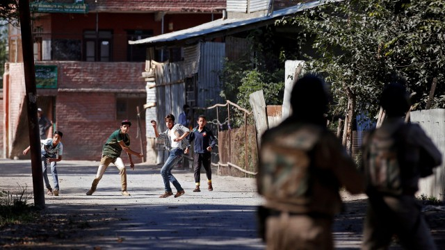 Youths hurl stones towards the Indian police during a protest against the recent killings in Kashmir, in Srinagar