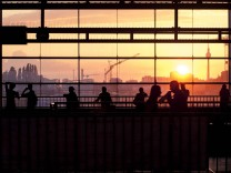 Germany Berlin S Bahn station Ostkreuz silhouettes of commuters at sunset PUBLICATIONxINxGERxSUIx