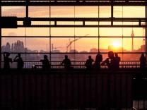 Germany Berlin S Bahn station Ostkreuz silhouettes of commuters at sunset PUBLICATIONxINxGERxSUIx