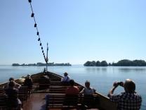 Touristen fahren mit einem Ausflugsschiff auf dem Chiemsee (Bayern) auf die Fraueninsel (l) und die unbewohnten Krautinsel zu
