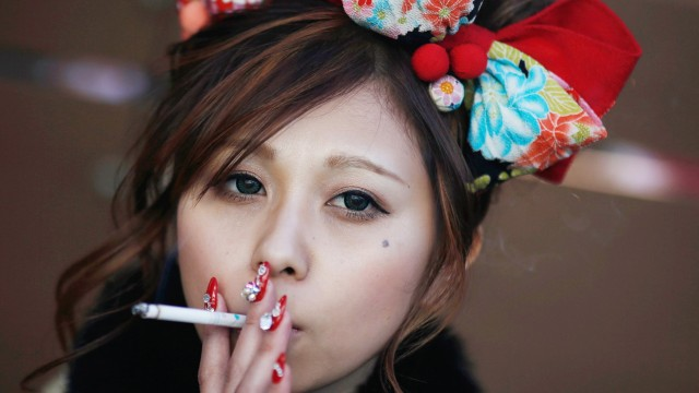 Mitomi holds a cigarette after a Coming of Age Day celebration ceremony at an amusement park in Tokyo