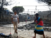 Migrants walk next to the remains of burned tents at the Moria migrant camp, after a fire that ripped through tents and destroyed containers during violence among residents, on the island of Lesbos
