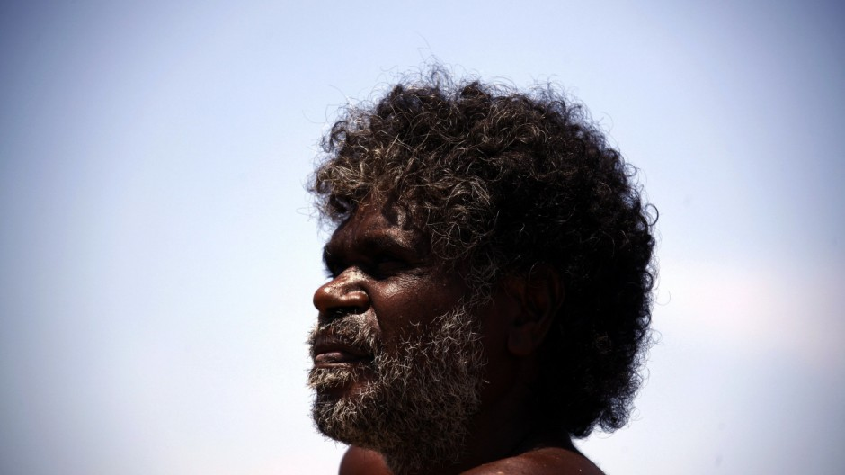 Australian Aboriginal hunter Bruce Gaykamangu looks across a billabong at potential prey near the 'out station' of Ngangalala, located on the outksirts of the community of Ramingining in East Arnhem Land