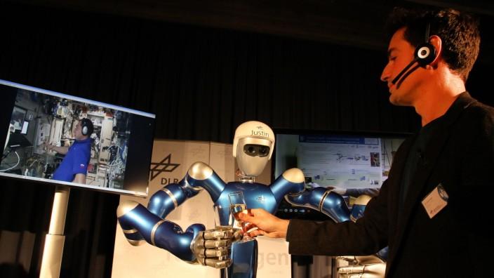 Mit ferngelenktem Roboterarm Hände schütteln; Händeschütteln mit Justin