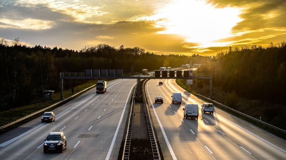 Autos und Lkw fahren auf der A2 bei Helmstedt Niedersachsen im Sonnenuntergang