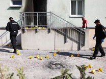 Police inspect the front of a mosque in Dresden, one day after an improvised bomb destroyed the entrance