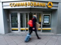 A pedestrian walks past a branch of Commerzbank in Frankfurt