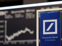A banners of Deutsche Bank is pictured in front of the German share price index, DAX in Frankfurt