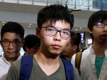 Pro-democracy activist Joshua Wong arrives at Hong Kong Airport after being deported from Bangkok