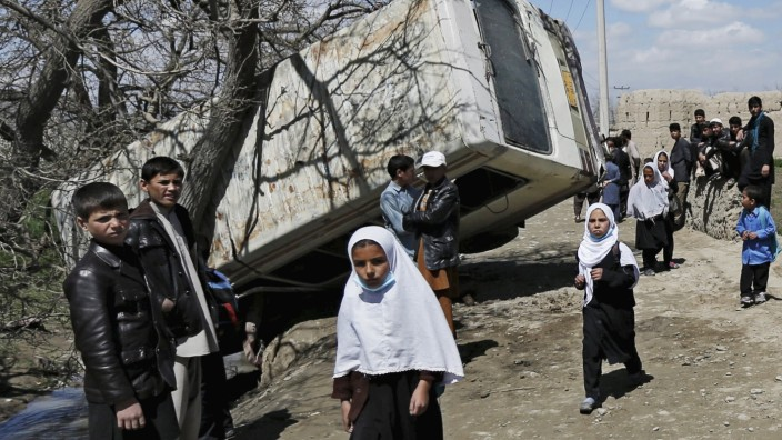 Schoolgirls walk past a damaged mini-bus after it was hit by a bomb blast in the Bagrami district of Kabul, Afghanistan