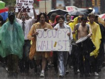 Demonstrators from the Occupy Wall Street campaign march in the rain through the streets of the financial district of New York