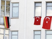 A German national flag is set up next to Turkish national flags at apartment building in Berlin