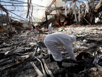 Forensic experts invistigate the scene at the community hall where Saudi-led warplanes struck a funeral in Sanaa, the capital of Yemen