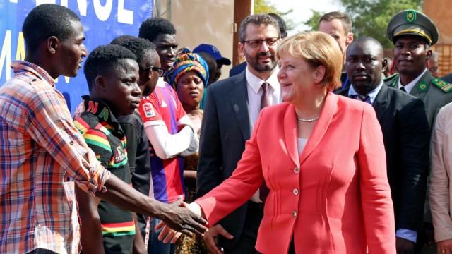 German chancellor Angela Merkel greets men at an International Organization for Migration transit center in Niamey