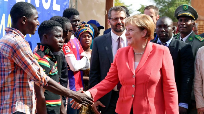 German chancellor Angela Merkel greets men at an International Organization for Migration transit center in Niamey