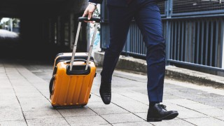 Businessman on business trip running with wheeled luggage model released Symbolfoto PUBLICATIONxINxG