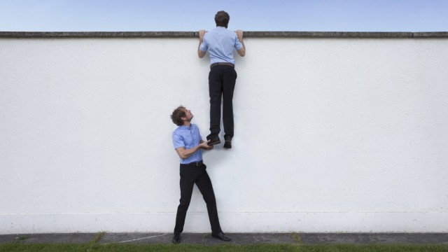 Business man helping colleague on wall model released Symbolfoto PUBLICATIONxINxGERxSUIxAUTxHUNxONLY