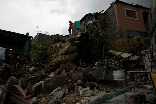 A woman stands next to destroyed houses after Hurricane Matthew hit Jeremie