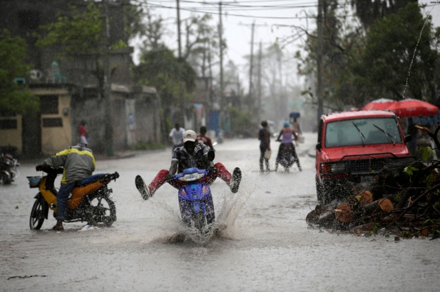 A man on a motorbike rides on a flooded street during rain after Hurricane Matthew in Les Cayes, Haiti