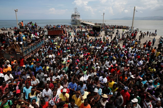 People wait for relief aid to be unloaded from a Dutch navy ship after Hurricane Matthew hit Jeremie