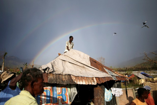 A man sets a tarpaulin to cover his house in an area destroyed by Hurricane Matthew in Les Anglais, Haiti