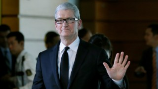 Apple Inc CEO Tim Cook waves after meeting with Japan's PM Abe at Abe's official residence in Tokyo