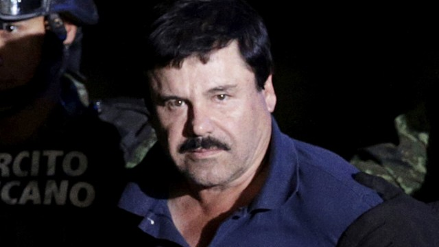 Recaptured drug lord Joaquin 'El Chapo' Guzman is escorted by soldiers at the hangar belonging to the office of the Attorney General in Mexico City