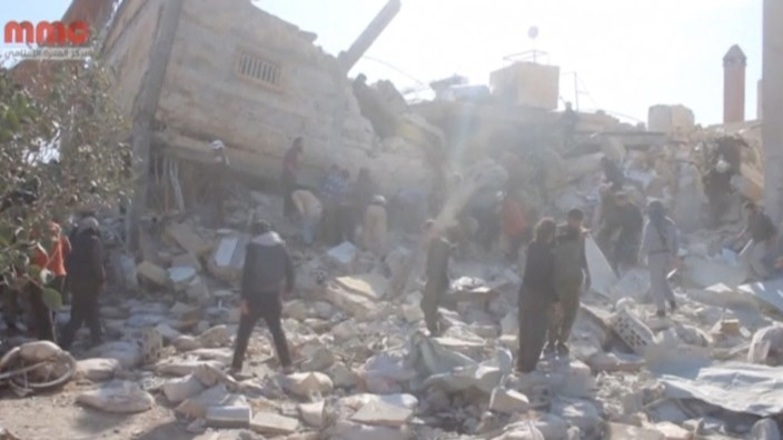 Still image taken from video shows people gathering near a destroyed building said to be a Medecins Sans Frontieres (MSF) supported hospital in Marat al Numan, Idlib, Syria