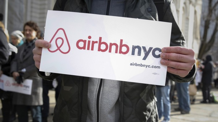 Supporters of Airbnb stand during a rally before a hearing at City Hall in New York
