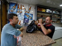 An Iraqi man buys alcohol from a wine shop in Baghdad, Iraq