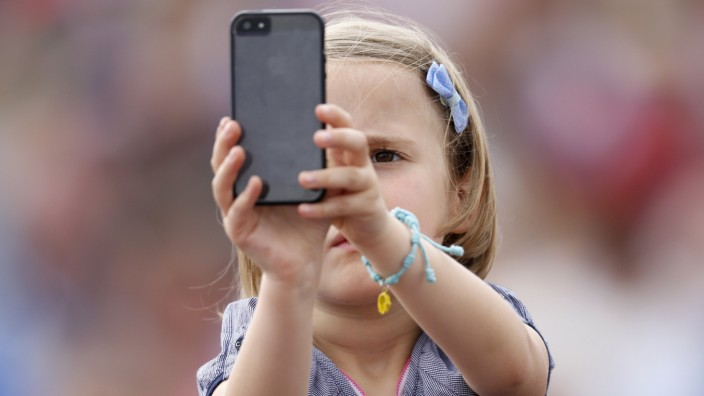 A child takes pictures with a mobile phone as Pope Francis leads the Angelus prayer at the Vatican