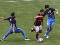 Flamengo s Diego c in action against Giovanni Augusto L and Romero R of Corinthians during th; Flamengo diego