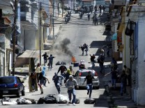 Demonstrators clash with riot police during a rally to demand a referendum to remove Venezuela's President Nicolas Maduro in San Cristobal