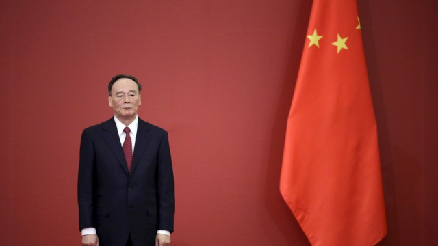 China's Politburo Standing Committee member Wang Qishan stands next to a Chinese flag in Beijing