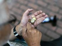 Ein Rentner zählt sein Kleingeld am Eingang zum Real Markt an der Weißhausstraße Köln 29 07 2016 F