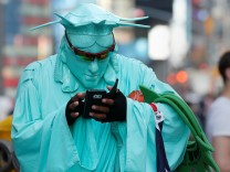 A person wearing a Statue of Liberty outfit to pose for tips checks his cell phone during warm weather in Times Square in the Manhattan borough of New York, New York