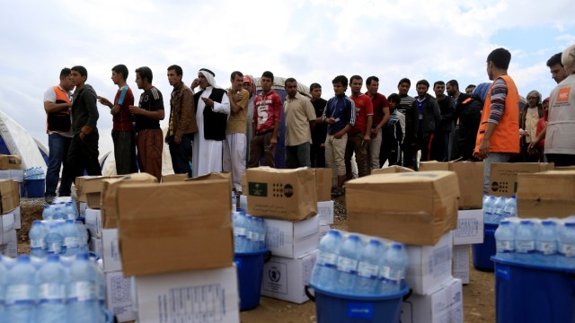 Newly internally displaced people queue to receive humanitarian packages at Al Khazer camp near Hassan Sham, east of Mosul