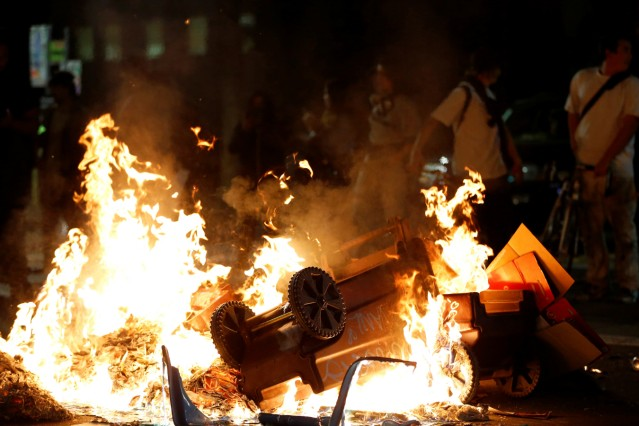A pile of burning garbage set by demonstrators is seen on Broadway during a demonstration in Oakland, California, U.S. following the election of Donald Trump as President of the United States