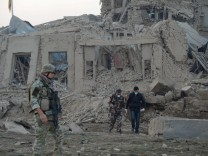 Afghan security forces and NATO troops investigate at the site of explosion near the German consulate office in Mazar-i-Sharif, Afghanistan