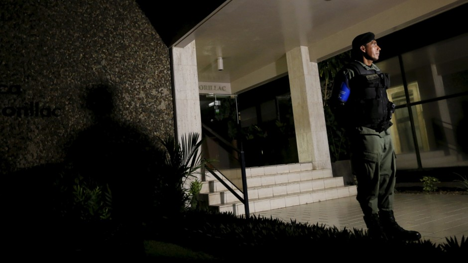 Police officers stand guard at the entrance of Mossack Fonseca law firm office late night in Panama City