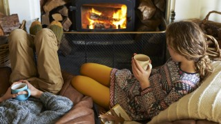 Children drinking cups of tea by fire