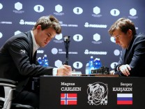 Magnus Carlsen, of Norway, takes notes during his match with Sergey Karjakin, of Russia, during their round 5 of the 2016 World Chess Championship in New York